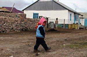Un bambino del villaggio di Sary Tash, Kyrgyzstan, cammina tra il vento gelido verso la propria abitazione