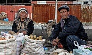 Nel bazar di Osh, Kyrgyzstan, un'anziana signora e suo figlio vendono alcune patate e delle verdure