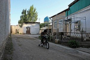 Un bambino gioca nella zona popolare chiusa da mura, vicino piazza Registan, Uzbekistan