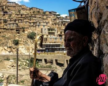 Anziano pastore curdo osserva il suo gregge pascolare tra le strette vie del paese. Palangan, Kurdistan iraniano