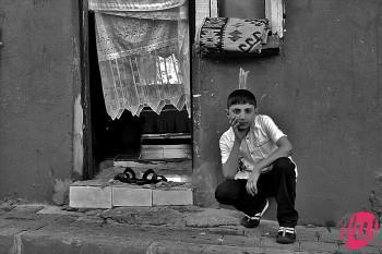 Un bambino davanti alla porta della sua abitazione. Istanbul, Turchia
