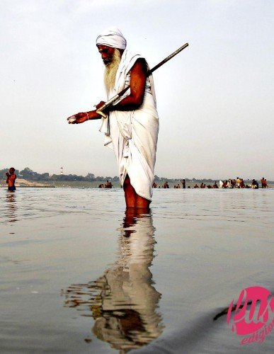 A Sadhu or a Hindu holy man offers milk to the waters of holy ri