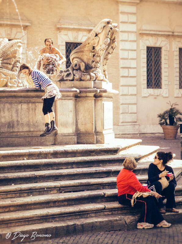 Racconto breve - L'immagine mostra due giovani che giocano lanciandosi acqua da una fontana pubblica