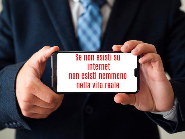 Cellulare tenuto da due mani con la scritta Se non esisti su internet non esisti nemmeno nella vita reale
