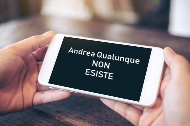 Cellulare tenuto da due mani con la scritta Andrea Qualunque non esiste