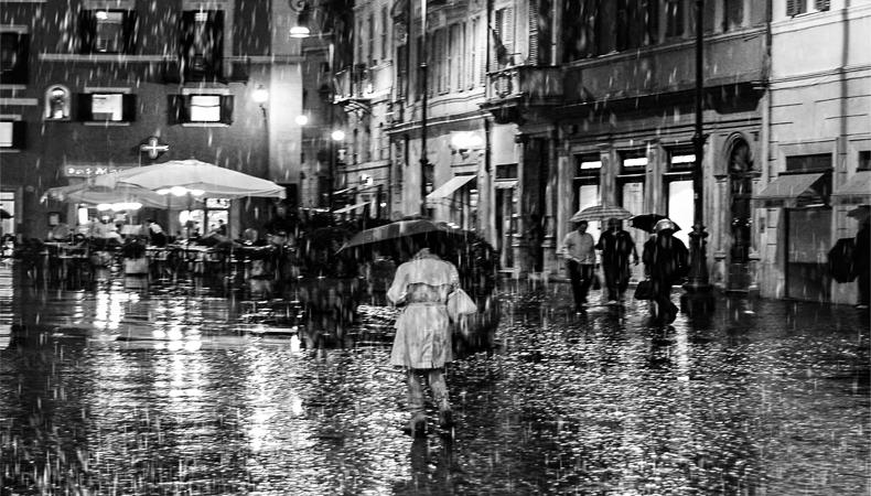 Foto in bianco e nero di una ragazza, di spalle, sotto la pioggia